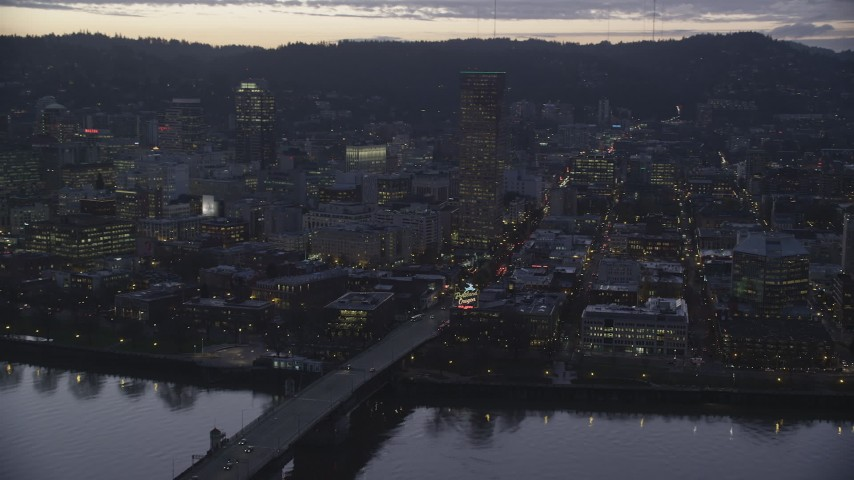 6K stock footage aerial video of the Burnside Bridge over the Willamette River, White Stag Sign, US Bancorp Tower at twilight, Downtown Portland, Oregon Aerial Stock Footage | AX155_255