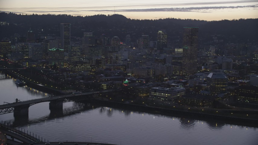 6K stock footage aerial video of Burnside Bridge over the Willamette River, White Stag Sign, skyscrapers at twilight, reveal Steel Bridge, Downtown Portland, Oregon Aerial Stock Footage | AX155_256