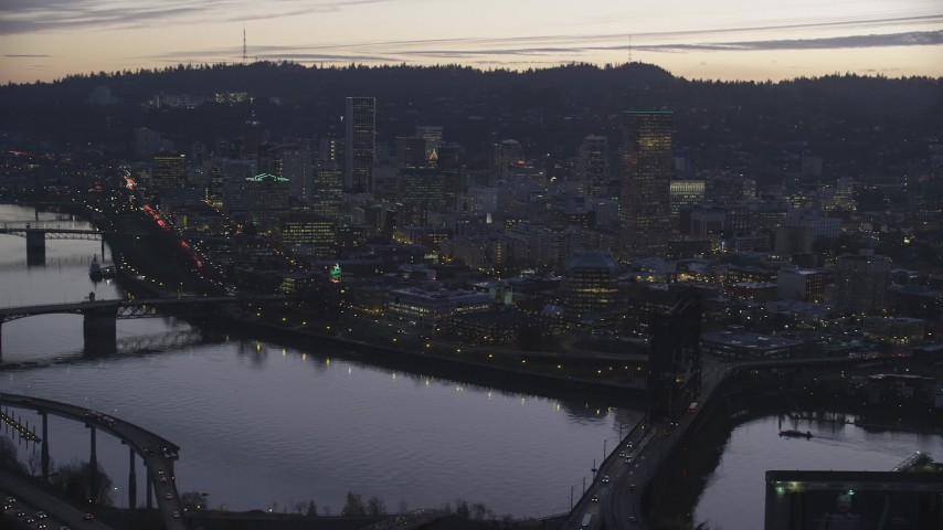 Steel Bridge over the Willamette River and skyscrapers at sunset, Downtown Portland, Oregon Aerial Stock Footage | AX155_257