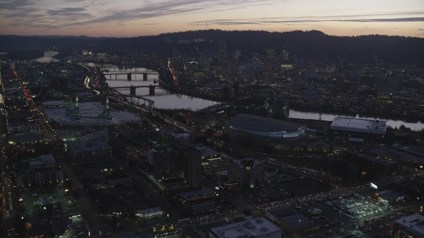 6K aerial video approaching Moda Center, Willamette River, and downtown skyscrapers at sunset, Downtown Portland, Oregon Aerial Stock Footage | AX155_260