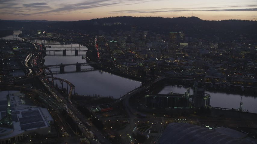 6K stock footage aerial video flying over Steel Bridge and Willamette River to approach downtown skyscrapers at twilight, Downtown Portland, Oregon Aerial Stock Footage | AX155_261