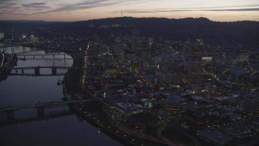 6K stock footage aerial video flying over downtown from the river and approach skyscrapers at twilight, Downtown Portland, Oregon Aerial Stock Footage | AX155_262