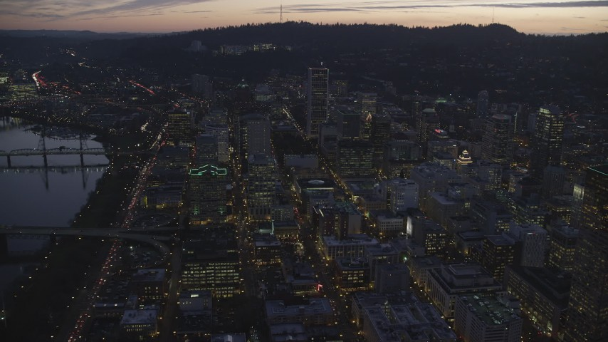 6K stock footage aerial video flying over downtown city streets and approach Wells Fargo Center at twilight, Downtown Portland, Oregon Aerial Stock Footage | AX155_263