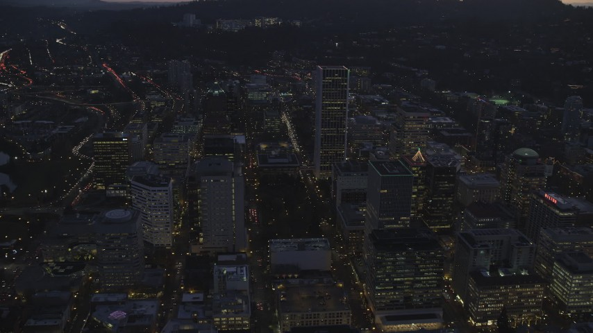6K stock footage aerial video following SW 3rd and 4th Avenues to approach KOIN Center and Wells Fargo Center at twilight, Downtown Portland, Oregon Aerial Stock Footage | AX155_264