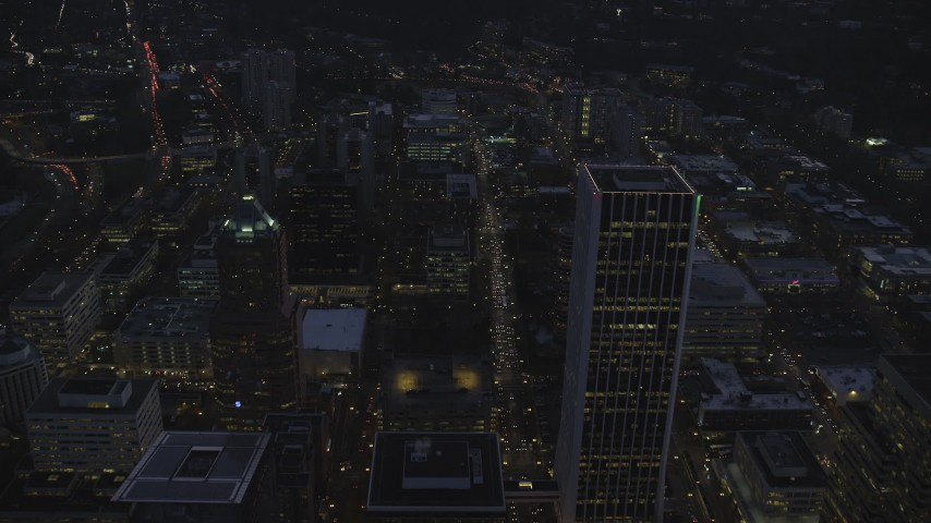 6K stock footage aerial video following SW 3rd and 4th Avenues between KOIN Center and Wells Fargo Center at twilight, Downtown Portland, Oregon Aerial Stock Footage   AX155_265