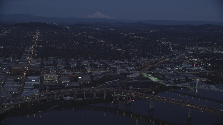 6K aerial video of Mount Hood in the far distance, and warehouse buildings near the Willamette River, Southeast Portland, Oregon, twilight Aerial Stock Footage | AX155_266