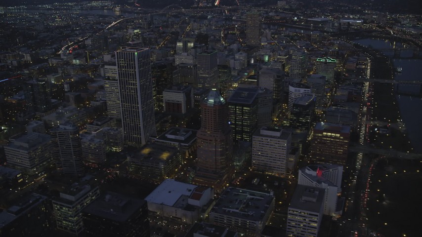6K stock footage aerial video flying away from KOIN Center and Downtown Portland cityscape beside the Willamette River at twilight, Oregon Aerial Stock Footage AX155_267 | Axiom Images