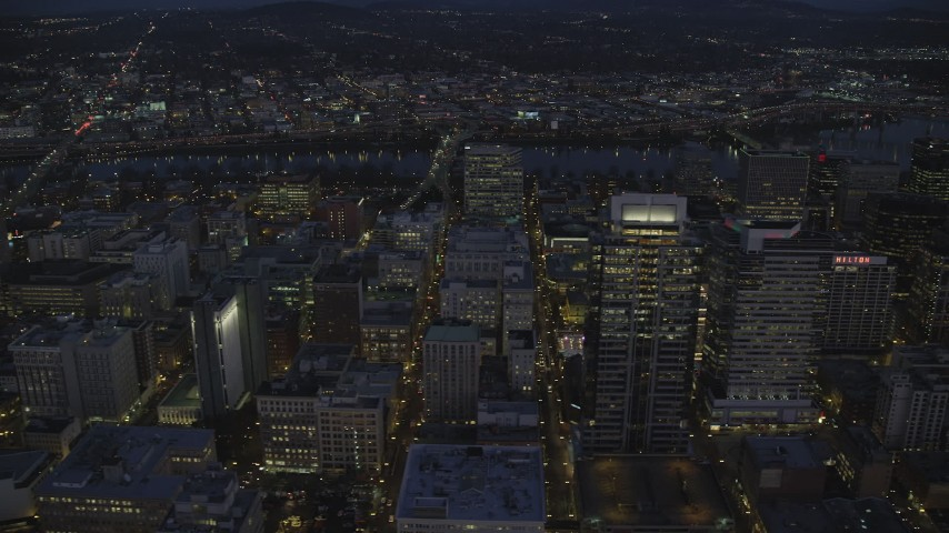 6K aerial video flying by Park Avenue West Tower in downtown, and reveal US Bancorp Tower at night in Downtown Portland, Oregon Aerial Stock Footage | AX155_273
