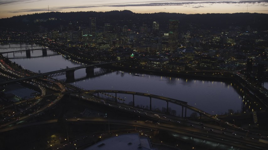 6K stock footage aerial video approaching freeway interchange, Willamette River, Burnside Bridge, and Downtown Portland, Oregon at twilight Aerial Stock Footage | AX155_278