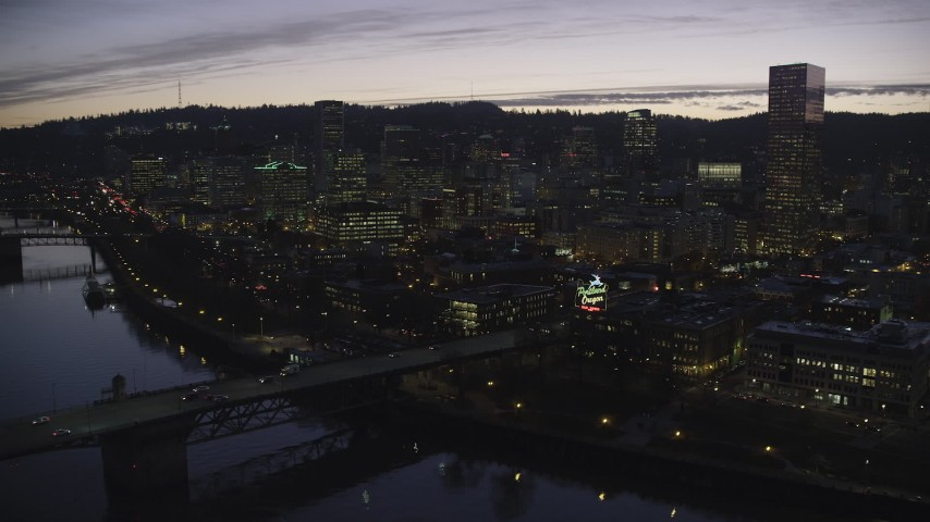 6K aerial video flying over the Burnside Bridge, White Stag sign, and approach Downtown Portland at twilight, Oregon Aerial Stock Footage | AX155_280