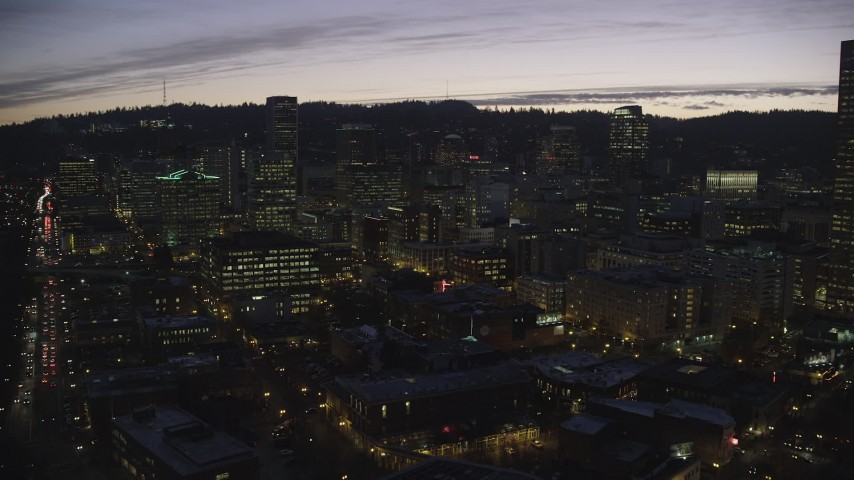 6K stock footage aerial video flying over downtown toward skyscrapers in Downtown Portland at twilight, Oregon Aerial Stock Footage | AX155_281