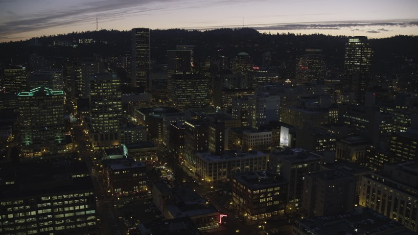 6K stock footage aerial video panning across downtown and follow SW 2nd Avenue in Downtown Portland at twilight, Oregon Aerial Stock Footage | AX155_282
