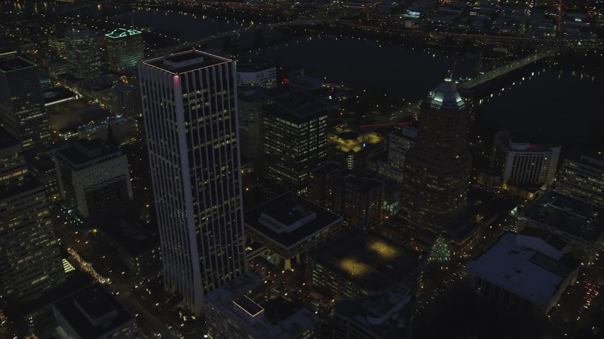 6K stock footage aerial video flying away from Wells Fargo Center and KOIN Center near the river at night in Downtown Portland, Oregon Aerial Stock Footage | AX155_289