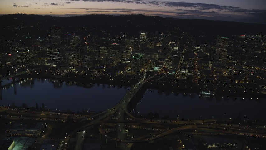 Downtown skyscrapers, Morrison Bridge, and Willamette River at night, Downtown Portland, Oregon Aerial Stock Footage | AX155_295