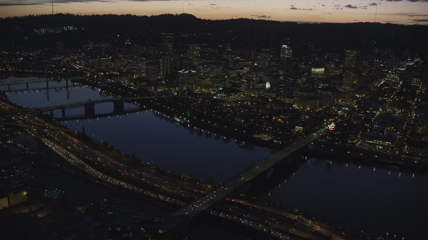6K stock footage aerial video of Downtown skyscrapers, Burnside Bridge, and White Stag sign at night, Downtown Portland, Oregon Aerial Stock Footage | AX155_296