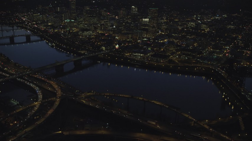 Downtown skyscrapers, Willamette River bridges, freeway interchange, and White Stag sign at night, Downtown Portland, Oregon Aerial Stock Footage | AX155_297