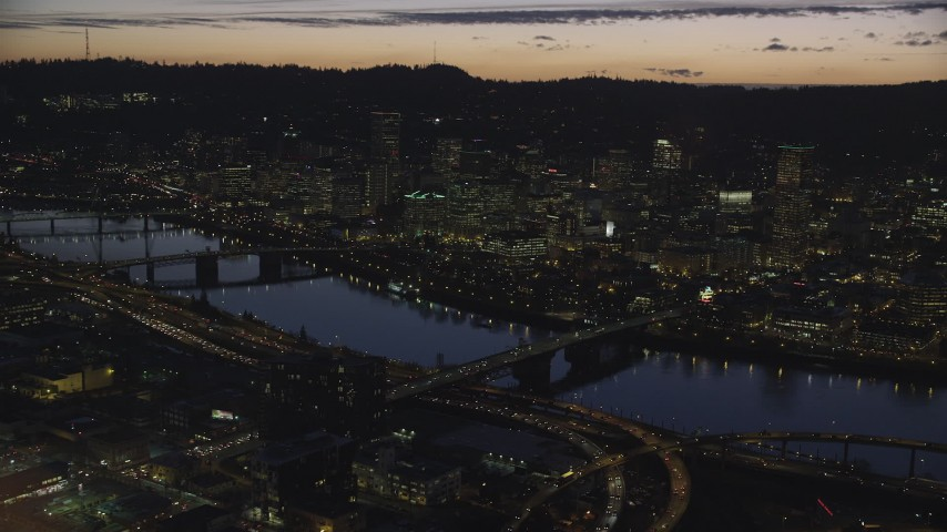 6K aerial video of a reverse view of downtown skyscrapers, Willamette River bridges, and freeway interchange at night, Downtown Portland, Oregon Aerial Stock Footage | AX155_298