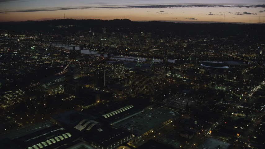 Approach office buildings, convention center, the Willamette River, and Downtown Portland at night in Oregon Aerial Stock Footage | AX155_299