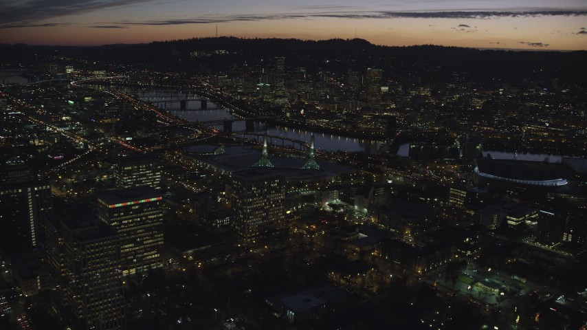 6K stock footage aerial video flying over convention center to approach the Willamette River and Downtown Portland at night in Oregon Aerial Stock Footage | AX155_300