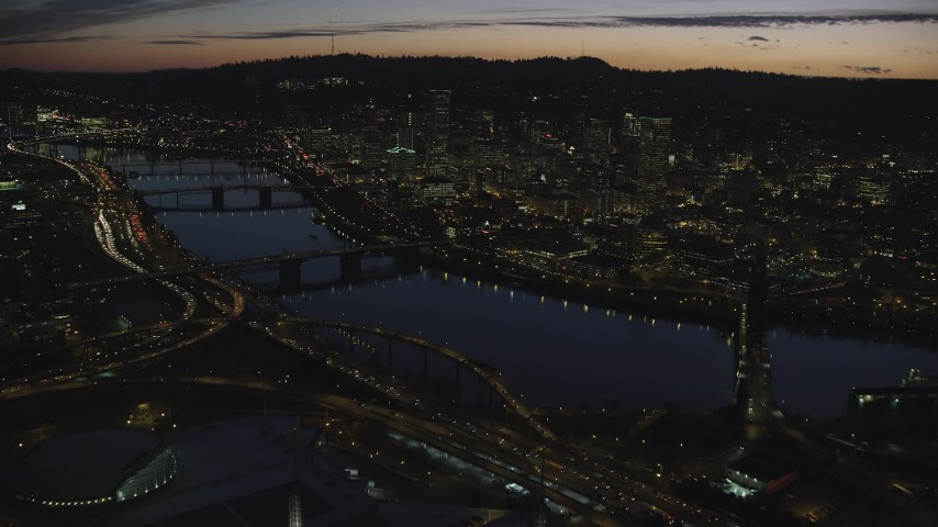 6K stock footage aerial video crossing the Willamette River to approach Burnside Bridge, White Stag Sign, and Downtown Portland at night in Oregon Aerial Stock Footage | AX155_301