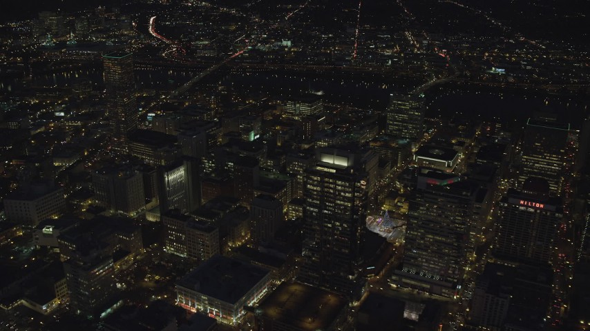 6K stock footage aerial video flying by Park Avenue West Tower and Fox Tower at night in Downtown Portland, Oregon, tilt to city streets Aerial Stock Footage | AX155_306