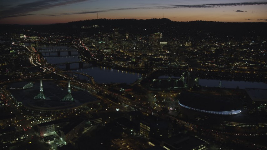 6K stock footage aerial video of Downtown Portland and Willamette River at night seen from Moda Center in Oregon Aerial Stock Footage | AX155_308