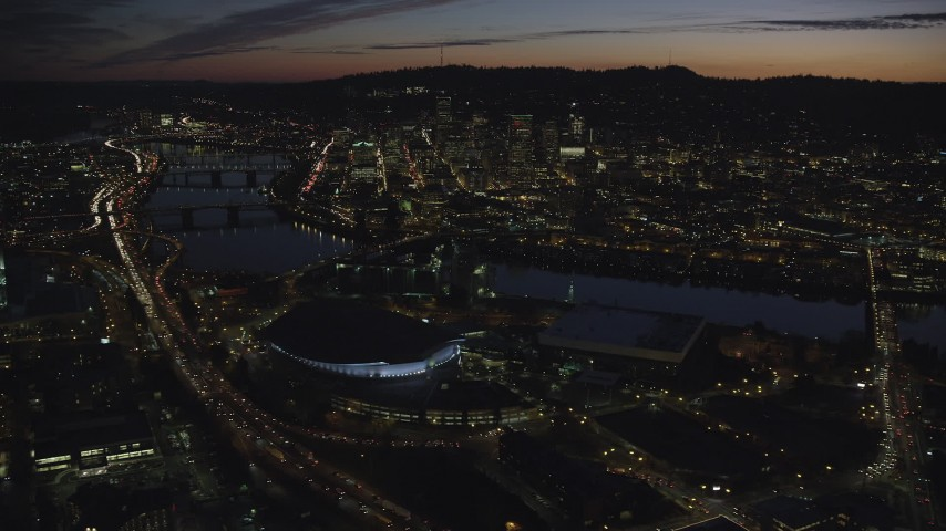 6K stock footage aerial video of Downtown Portland and Willamette River at night seen from Moda Center and Memorial Coliseum in Oregon Aerial Stock Footage | AX155_309