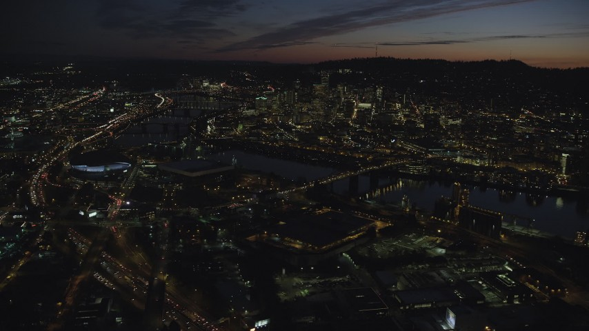6K stock footage aerial video approaching Moda Center, Memorial Coliseum, and Willamette River, with a view of Downtown Portland, Oregon, night Aerial Stock Footage | AX155_311