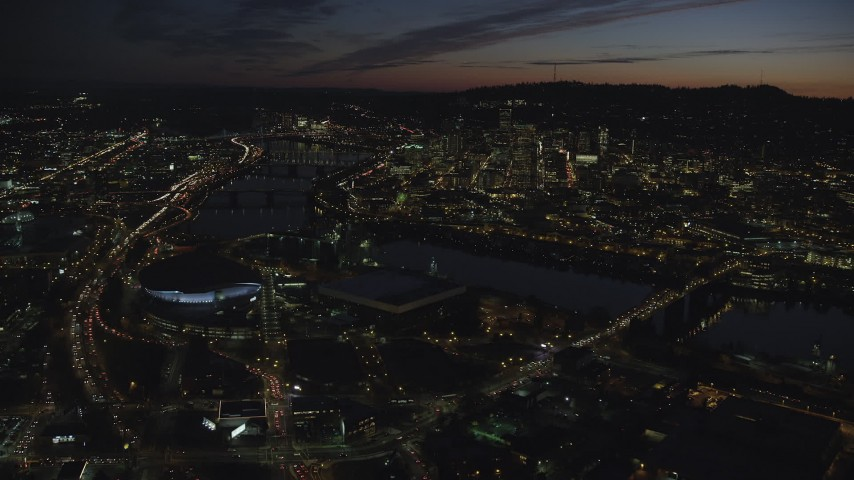6K stock footage aerial video approaching Moda Center, Memorial Coliseum by the Willamette River, with a view of Downtown Portland, Oregon, night Aerial Stock Footage | AX155_312