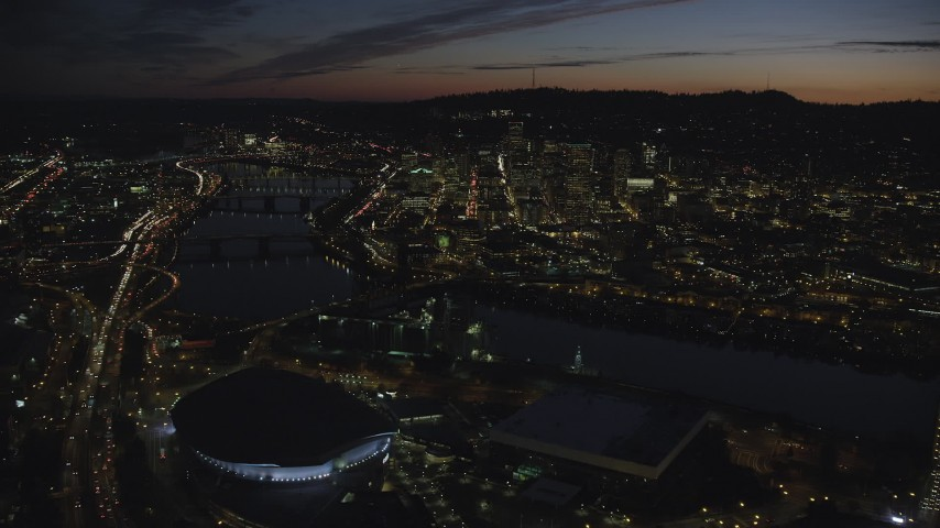 6K stock footage aerial video flying over Moda Center, Memorial Coliseum by the Willamette River, with a view of Downtown Portland, Oregon, night Aerial Stock Footage | AX155_313