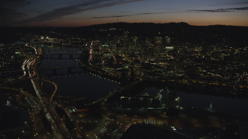 A view of Downtown Portland, Oregon, at night across the Willamette River Aerial Stock Footage   AX155_314