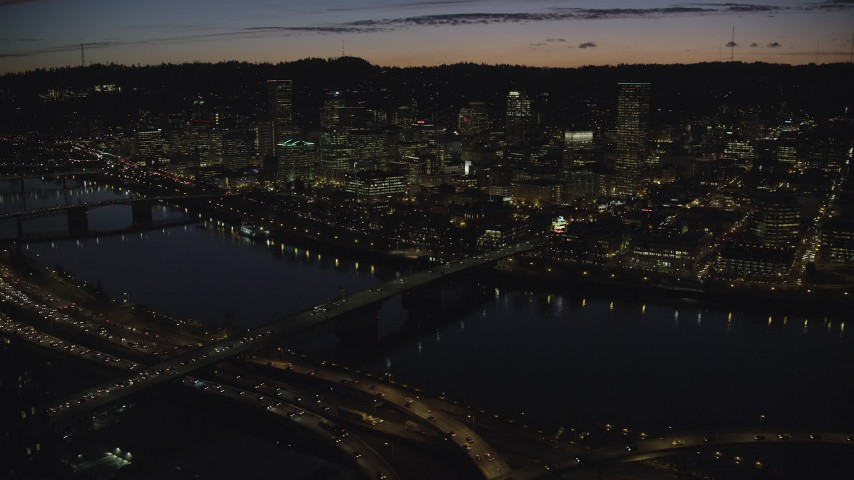 6K stock footage aerial video of a view across the Burnside Bridge and Willamette River of Downtown Portland and the White Stag Sign, Oregon, at night Aerial Stock Footage | AX155_317