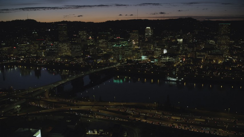 6K stock footage aerial video of Downtown Portland skyscrapers at night seen across the Morrison Bridge and Willamette River, Oregon Aerial Stock Footage | AX155_319