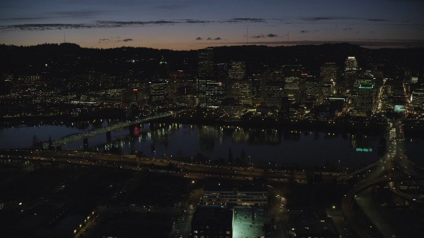6K stock footage aerial video of Downtown Portland skyscrapers at night seen across the Hawthorne Bridge and Willamette River, Oregon Aerial Stock Footage | AX155_320