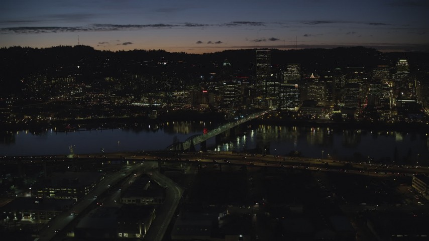 6K stock footage aerial video of Downtown Portland skyscrapers at night seen across the Hawthorne Bridge spanning Willamette River, Oregon Aerial Stock Footage | AX155_321