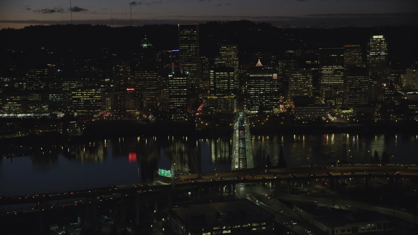 6K stock footage aerial video of Downtown Portland skyscrapers at night across the Hawthorne Bridge spanning Willamette River, Oregon Aerial Stock Footage | AX155_322