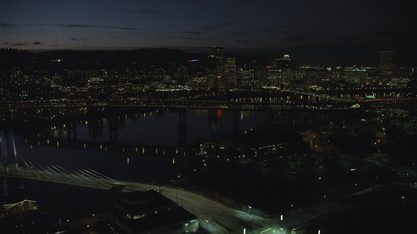 6K stock footage aerial video flying by Tilikum Crossing, with Downtown Portland skyline in the distance, Oregon, night Aerial Stock Footage | AX155_323