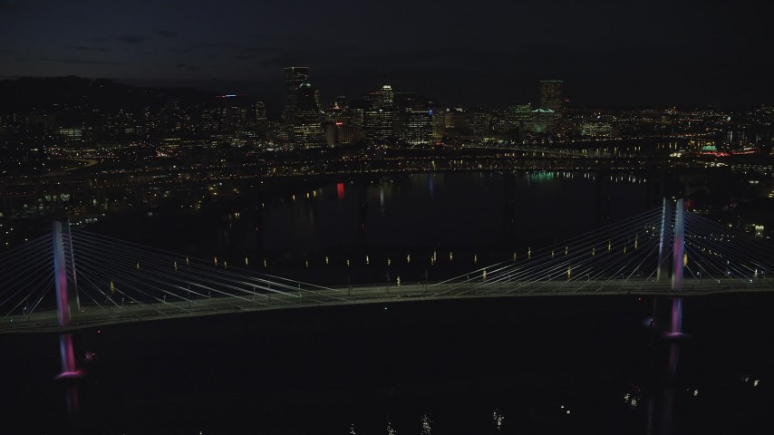 6K aerial video of Tilikum Crossing as it changes colors and Marquam Bridge, with Downtown Portland skyline in the distance, Oregon, night Aerial Stock Footage | AX155_325
