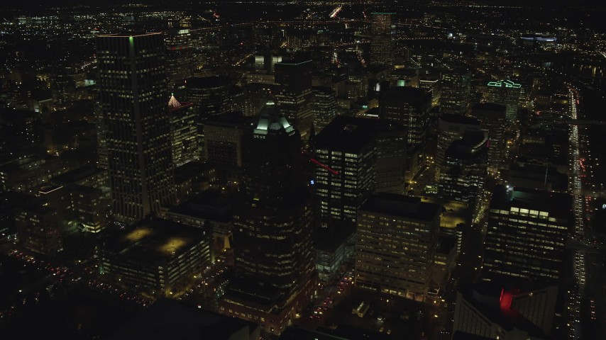 6K stock footage aerial video flying over KOIN Center and Wells Fargo Center, and reveal city squares at night in Downtown Portland, Oregon Aerial Stock Footage | AX155_329