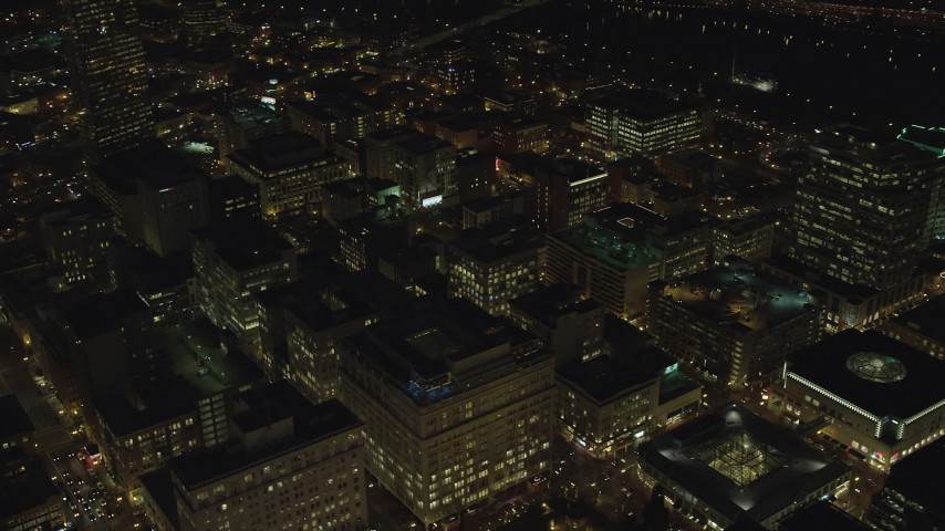 6K stock footage aerial video orbiting city buildings at night in Downtown Portland, Oregon, and reveal the busy streets Aerial Stock Footage | AX155_330