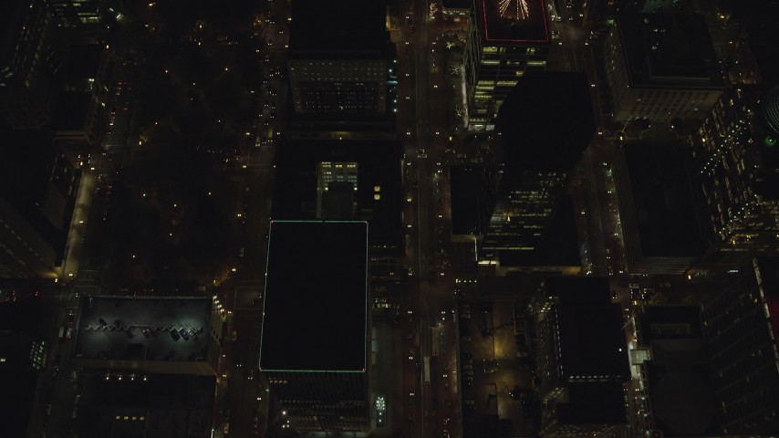 6K stock footage aerial video of a bird's eye of buildings between SW 4th and SW 5th Avenue at night through Downtown Portland, Oregon, reveal Wells Fargo Center Aerial Stock Footage | AX155_337