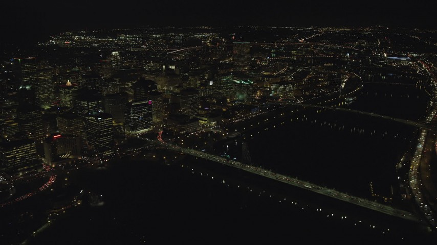 6K aerial video flying by the Downtown Portland cityscape, and bridges over the Willamette River at nighttime Aerial Stock Footage | AX155_359