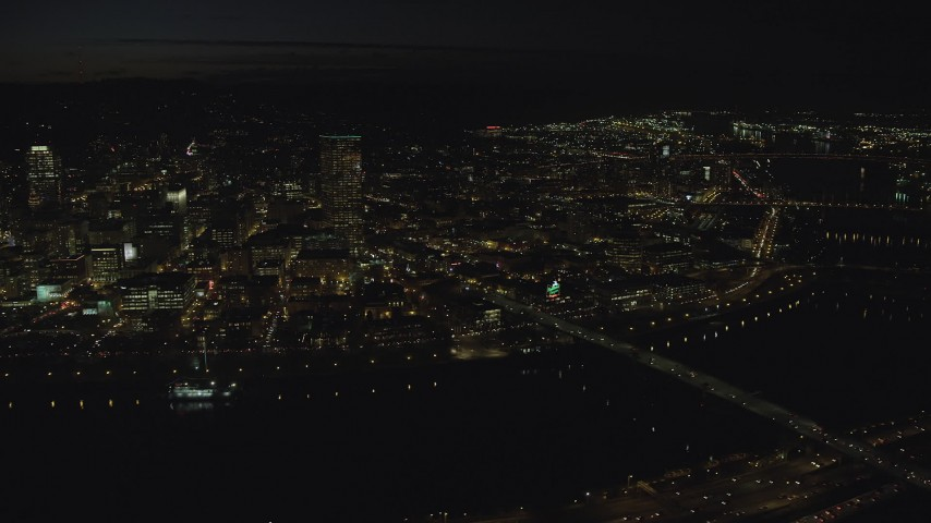 6K stock footage aerial video of US Bancorp Tower and the White Stag sign across the Willamette River and Burnside Bridge, night, Downtown Portland, Oregon Aerial Stock Footage | AX155_361