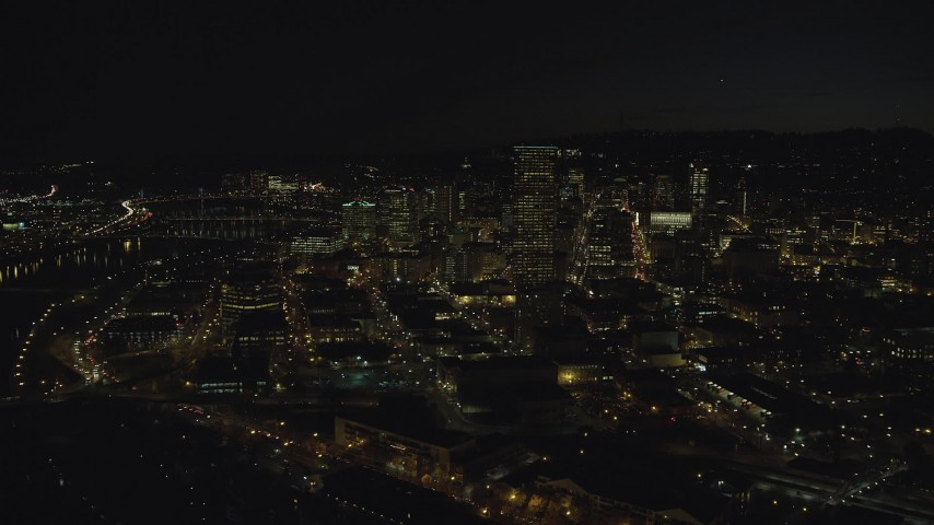 6K stock footage aerial video approaching US Bancorp Tower and skyscrapers by the Willamette River at nighttime, Downtown Portland, Oregon Aerial Stock Footage | AX155_365