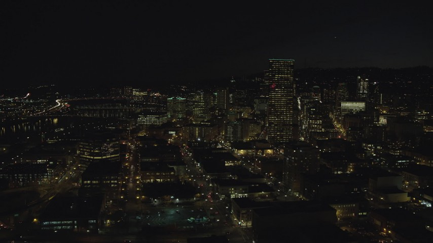 6K stock footage aerial video of US Bancorp Tower and skyscrapers by the Willamette River at nighttime, Downtown Portland, Oregon Aerial Stock Footage | AX155_366