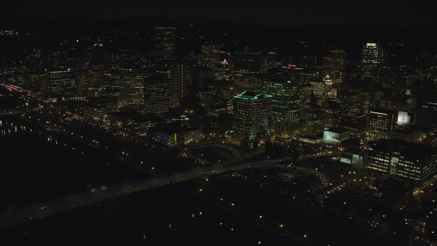 6K stock footage aerial video of Downtown Portland high-rises seen from the Morrison Bridge at night, Oregon Aerial Stock Footage | AX155_372