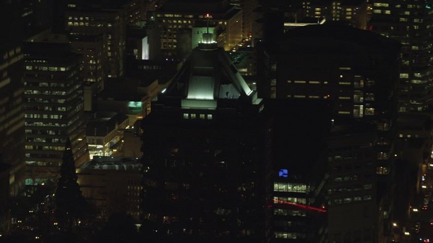6K stock footage aerial video orbiting of the KOIN Center rooftop venting steam at night in Downtown Portland, Oregon Aerial Stock Footage | AX155_377