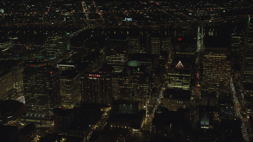 6K stock footage aerial video flying by high-rises and skyscrapers by the Willamette River at night in Downtown Portland, Oregon Aerial Stock Footage | AX155_392