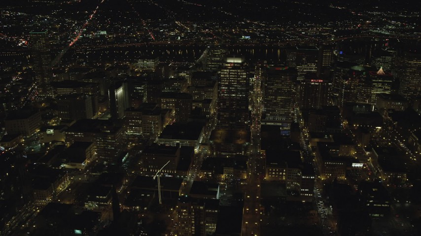 6K stock footage aerial video flying by and approaching downtown high-rises, skyscrapers, and busy streets at nighttime in Downtown Portland, Oregon Aerial Stock Footage | AX155_402