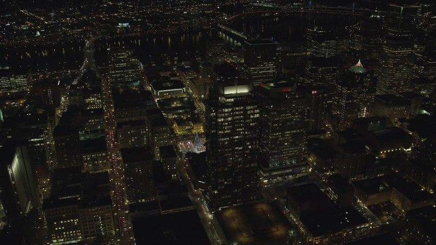 6K stock footage aerial video flying over skyscrapers to reveal Christmas tree in Pioneer Courthouse Square at night in Downtown Portland, Oregon Aerial Stock Footage | AX155_403